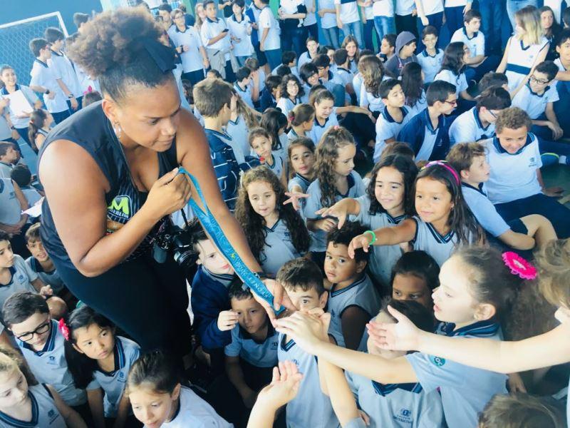 Tati Motta, pivô do Poty/BAX Catanduva, leva a medalha de Sydney-2000 aos pequenos da Escola Graciema / Foto: Divulgação/IJA